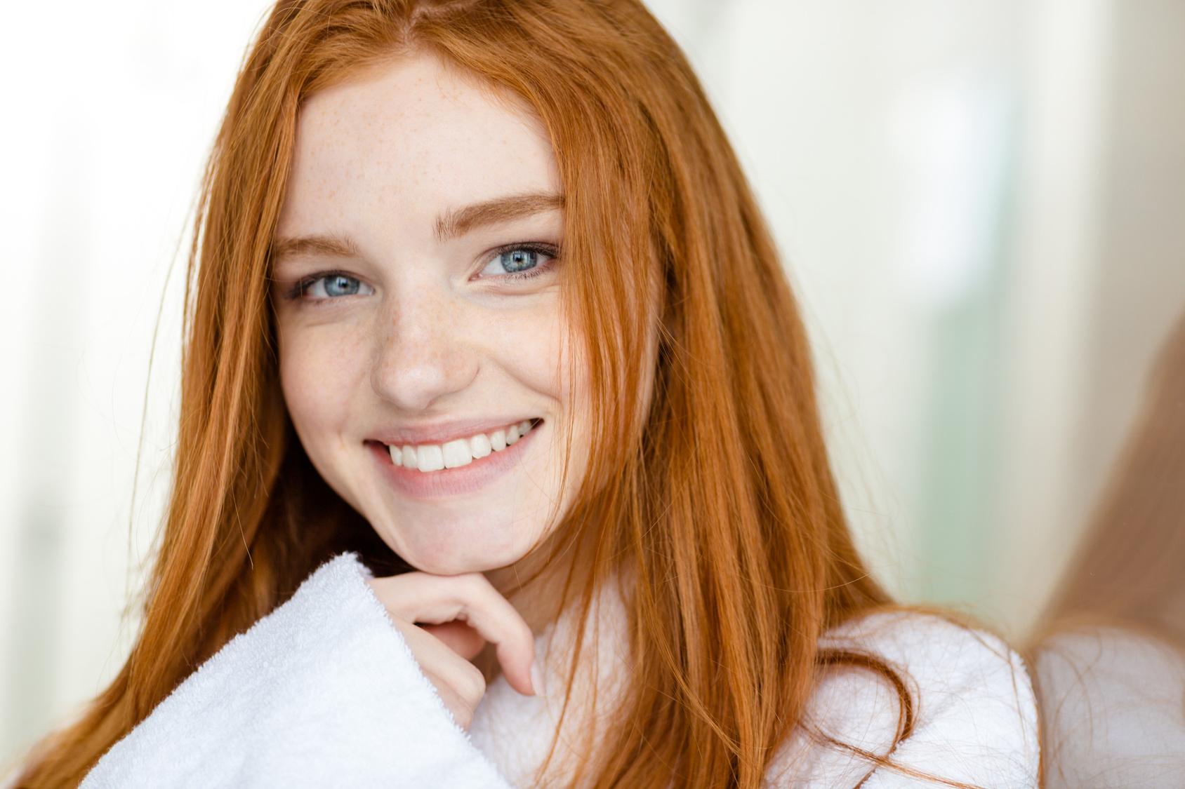 Portrait of a happy redhead woman in bathrobe